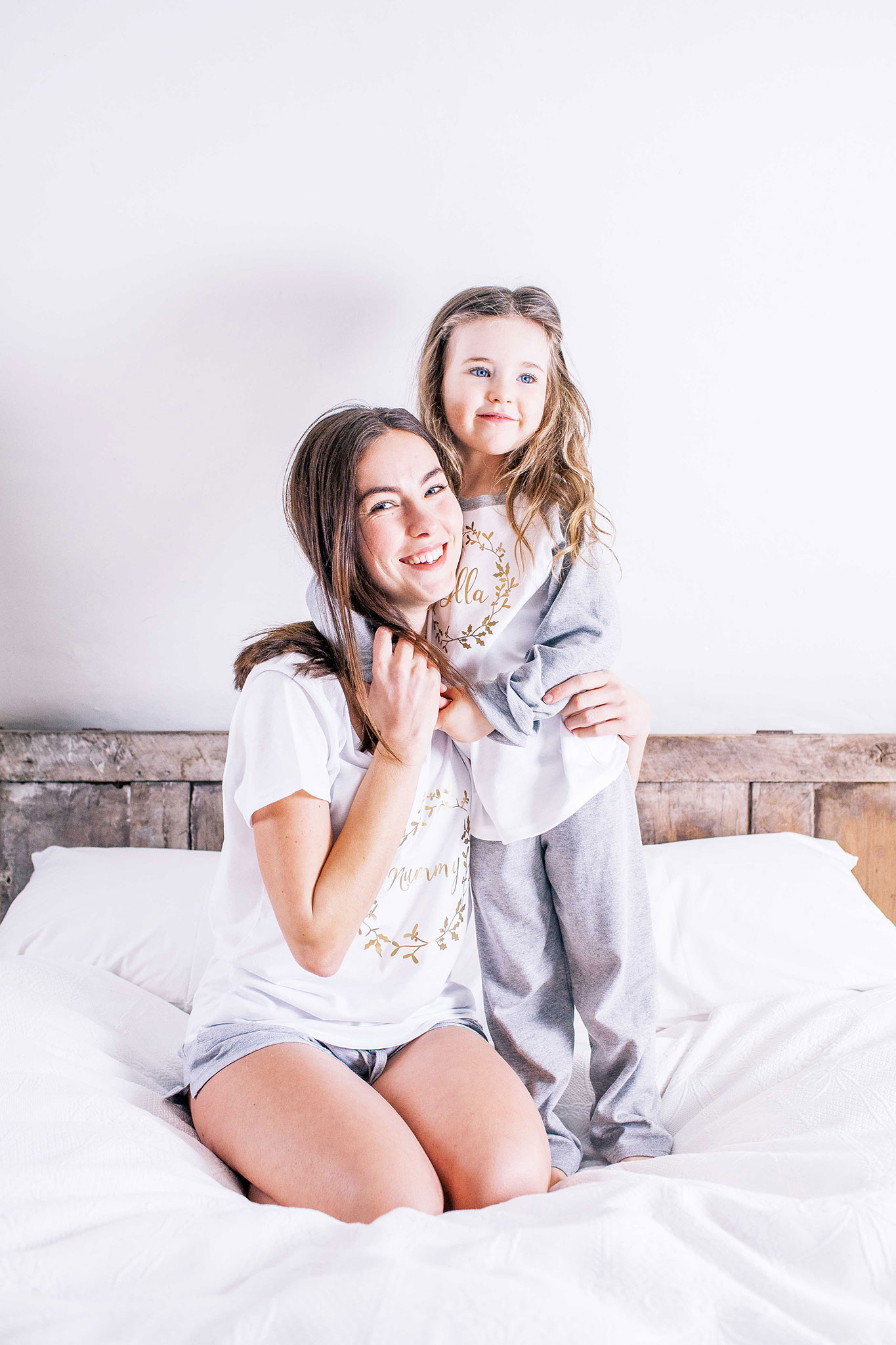 mom and daughter in matching pyjamas on white linen