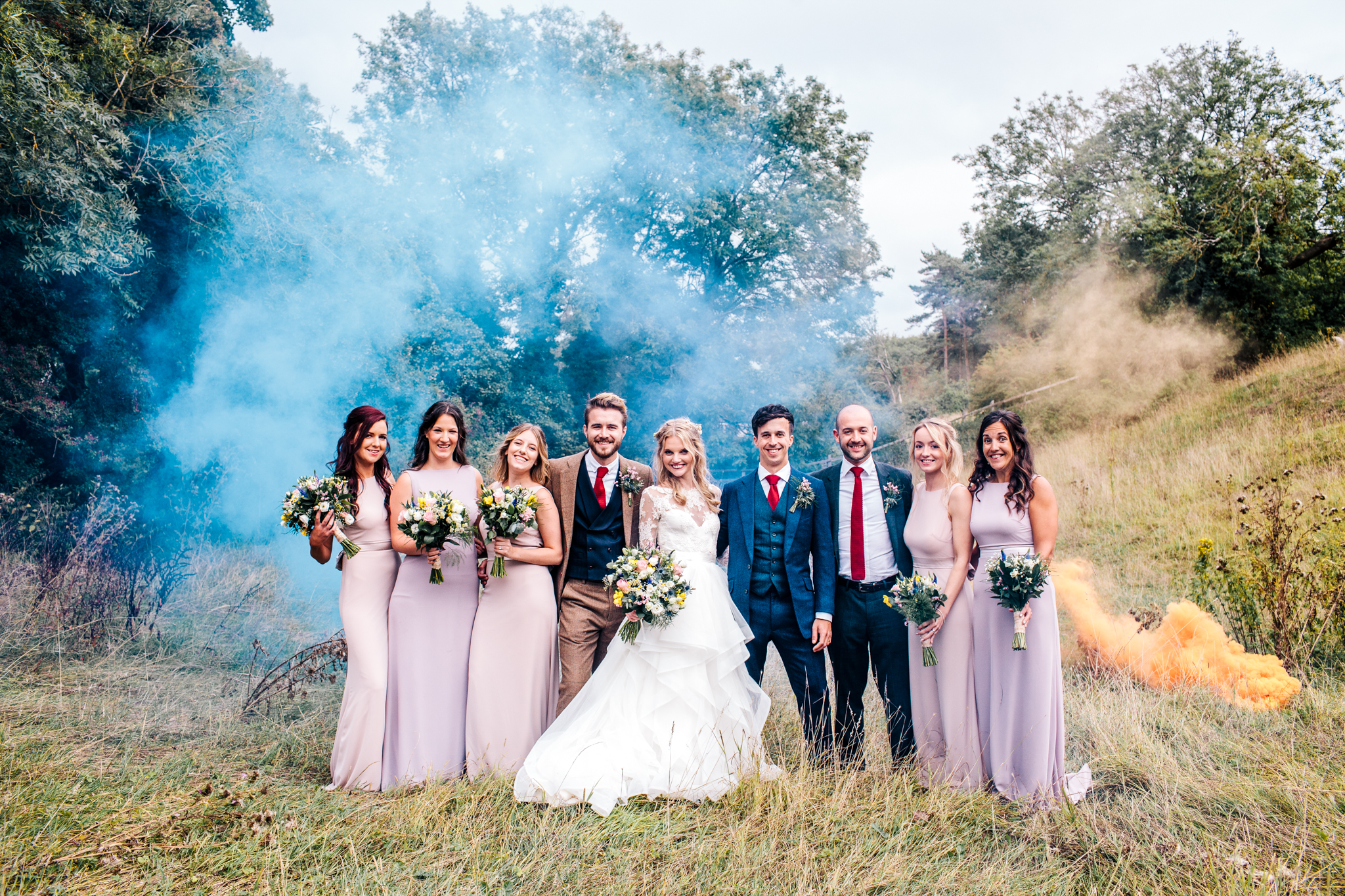 smoke bomb field photo with epic wedding party and Hayley Paige dress