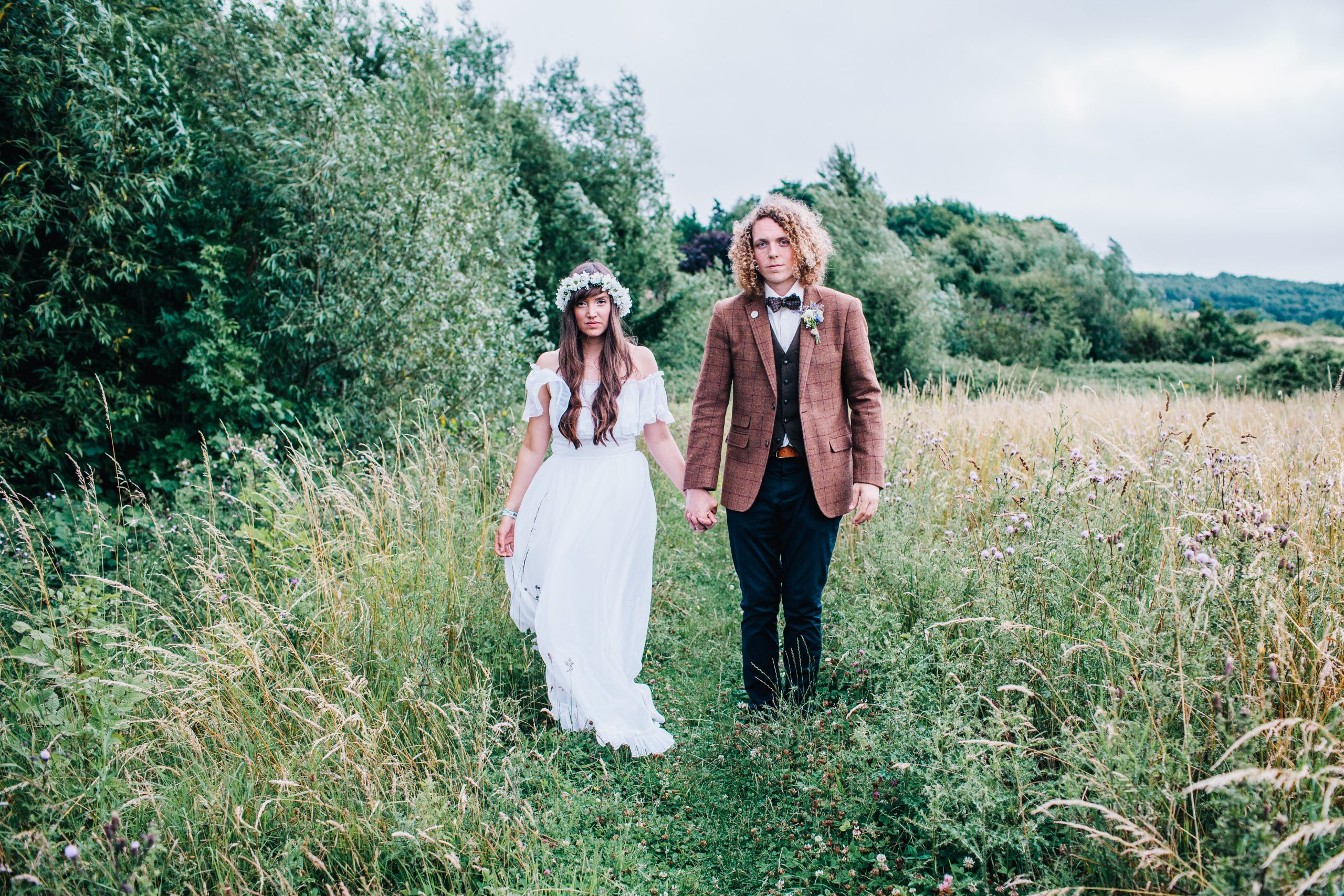outdoor festival wedding with bride wearing charity shop wedding dress walking holding hands with groom in tweed