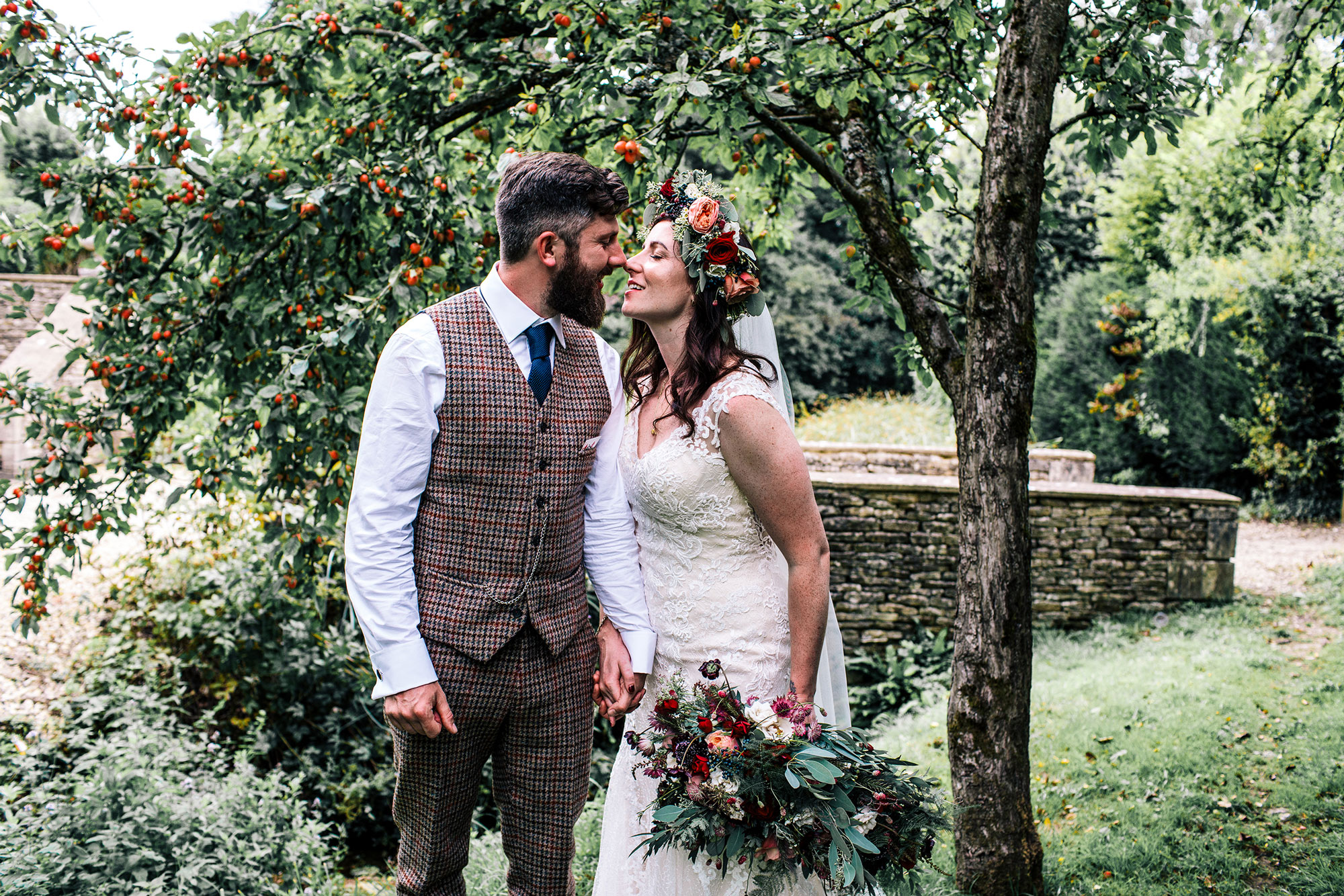 alternative bride and groom with peach and red florals standing and kissing under apple tree at owl pen manor
