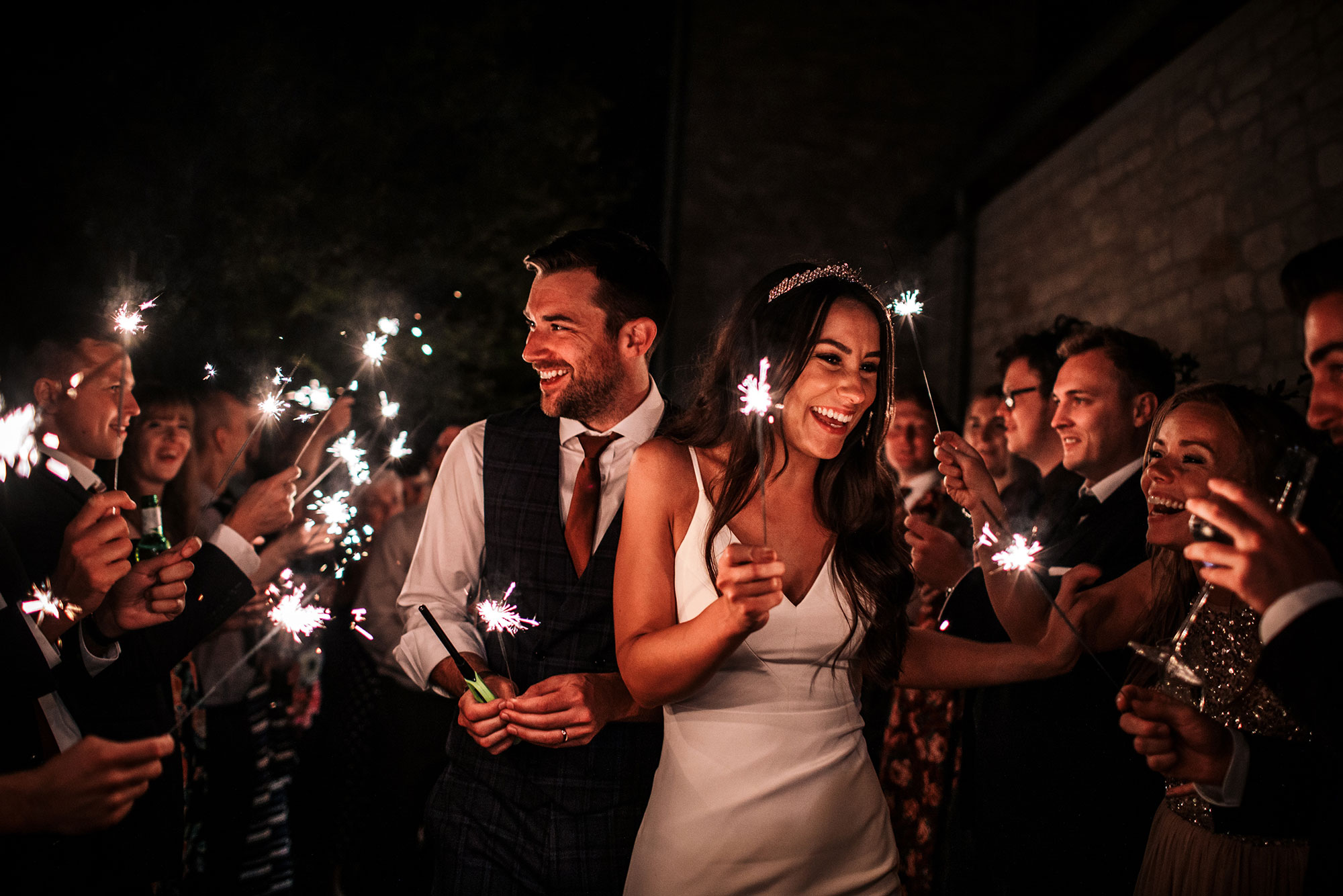 Bride and groom walking holding sparklers late at night in bath