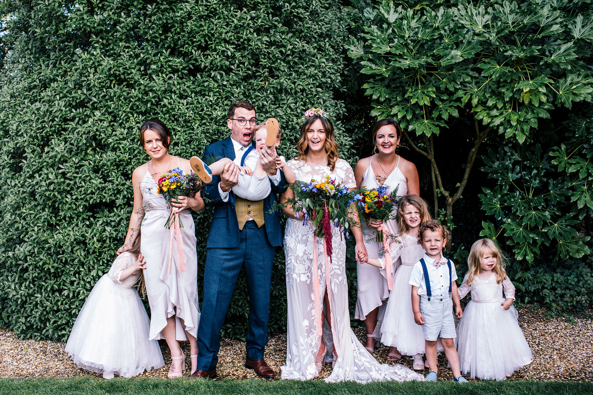 group photo of groom lifting up kid who is mis behaving to get him to laugh at pennard house somerset
