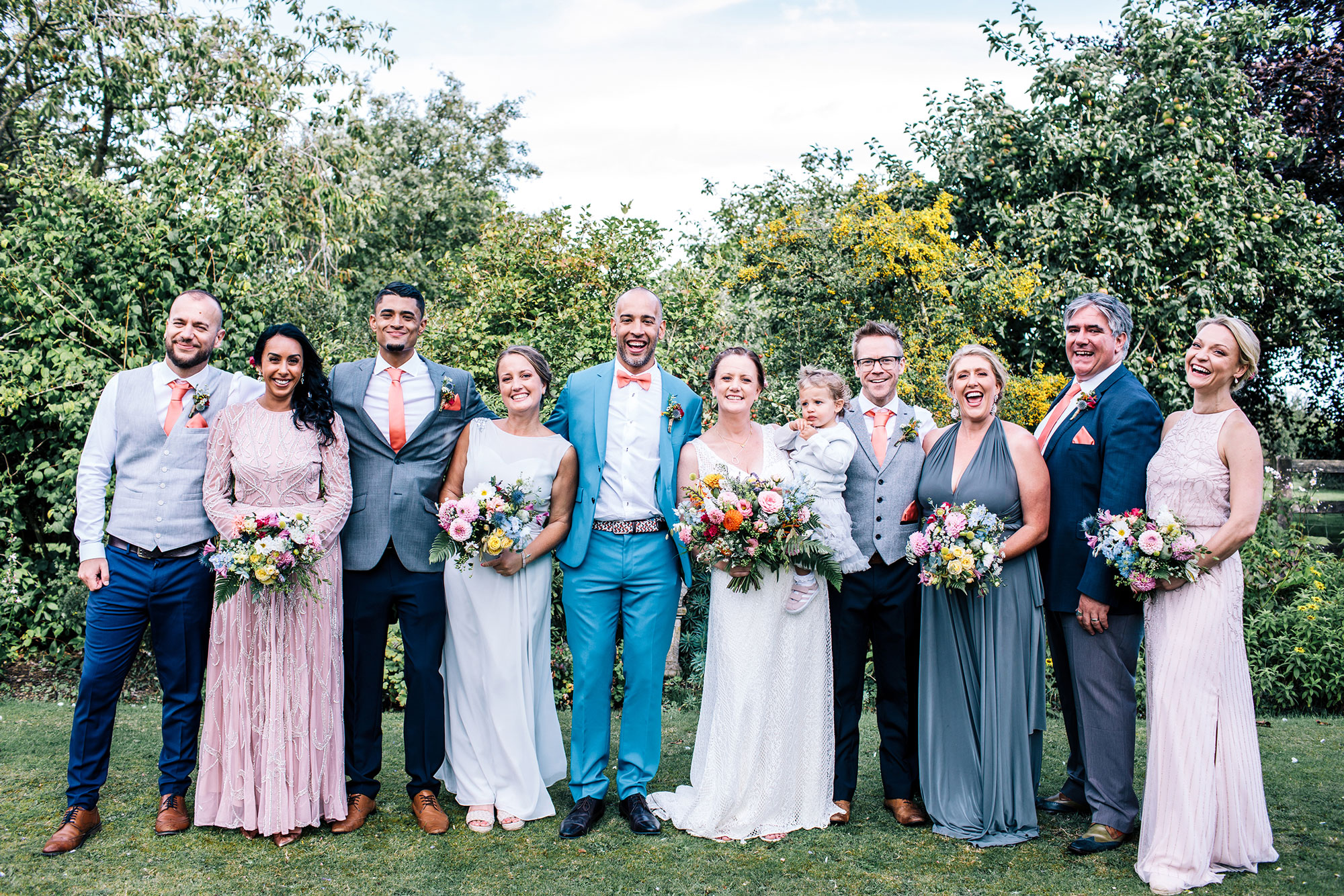 groom wearing bright blue wedding suit standing for a group shot with his bride and family at Seymour court wedding venue in beckington