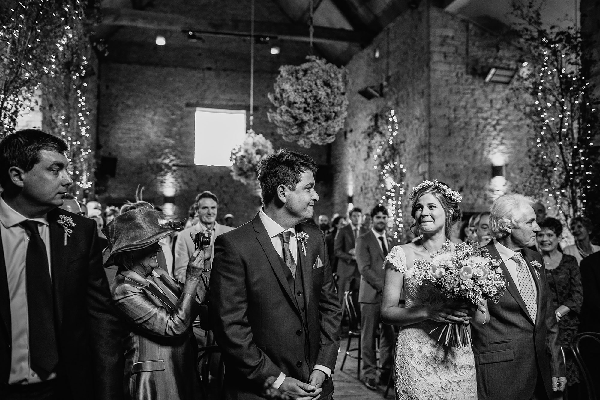 bride biting lip at groom as she walks down the aisle at Cripps barn near Worcestershire
