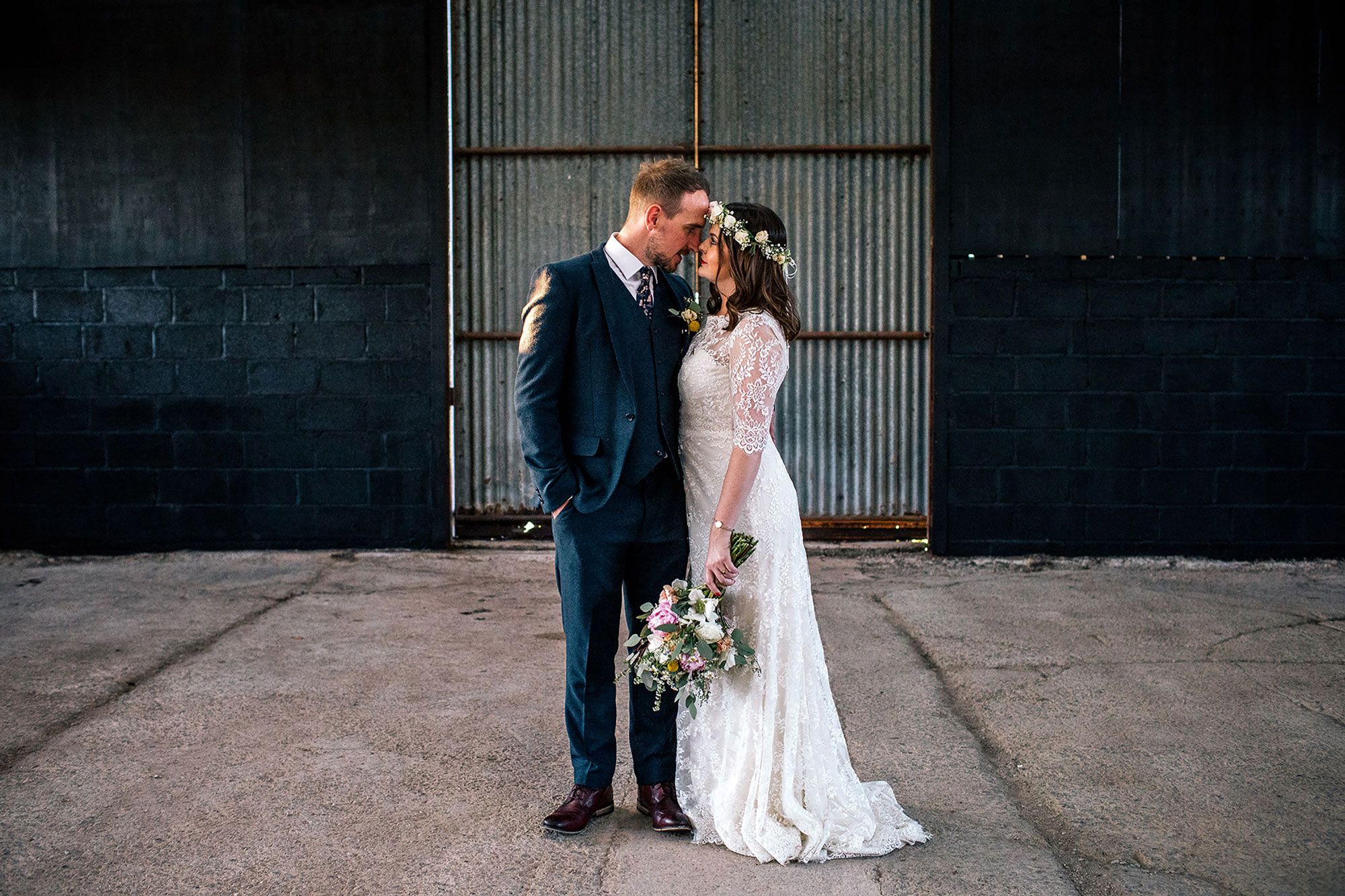 bride and groom standing in a dark cow shed for their wedding portraits at Curradine barns Worcestershire